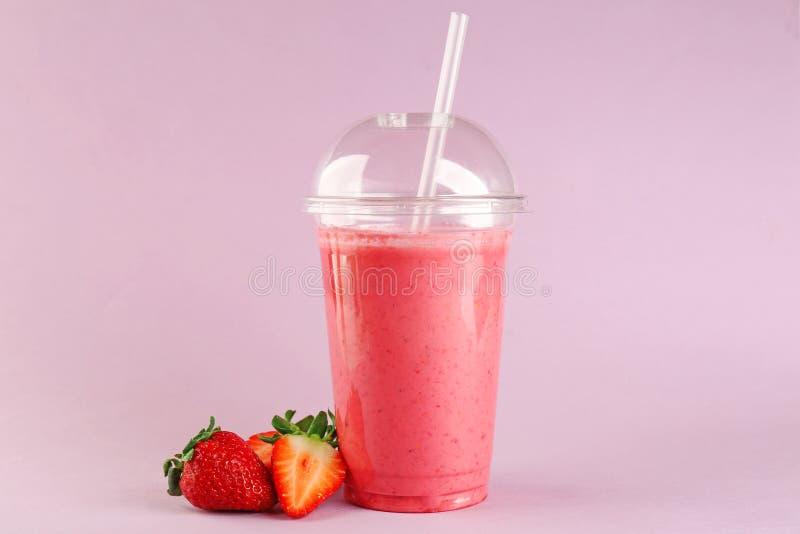 Läcker jordgubbemilkshake i plast- kopp arkivbild