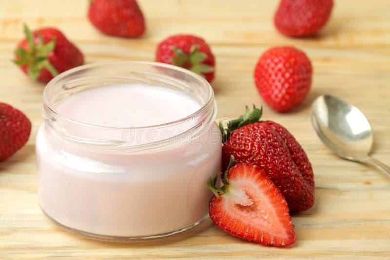 Läcker jordgubbeyoghurt i en krus och nya mogna jordgubbar på en naturlig trätabell arkivbild