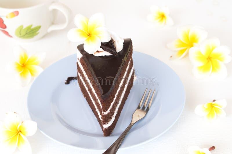 Läcker kaka för efterrättmellanmålchoklad och koppkaffe med blommafrangipanien royaltyfria foton