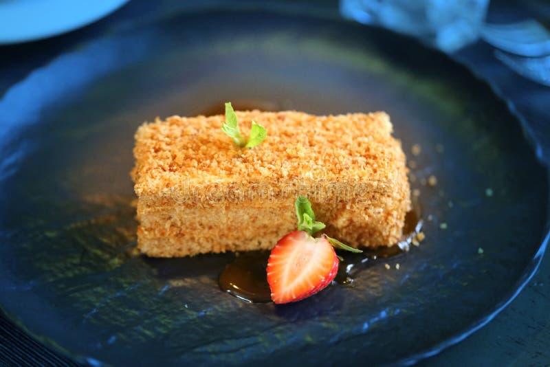 Läcker kaka med honung och jordgubbar på plattan arkivfoton