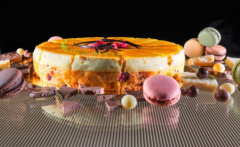Läcker kaka som omges av makron och chokladsötsaker arkivfoton