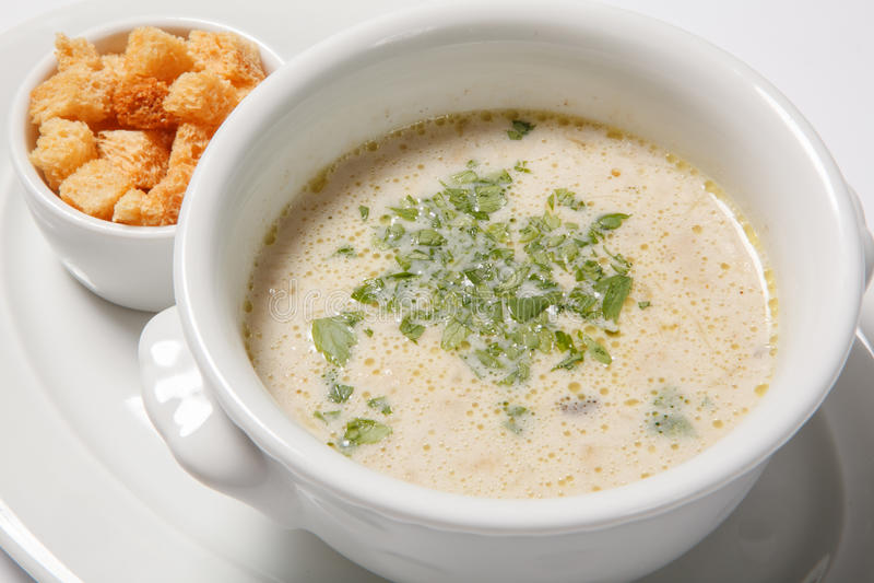Läcker krämig soppa med krutonger och gräsplaner på den vita maträtten arkivbilder