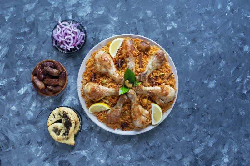 Läcker kryddig höna Biryani i den vita bunken på svart indisk eller pakistansk mat för bakgrund, arkivbild