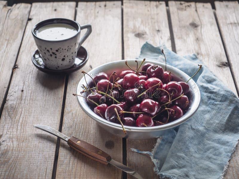 Läcker lunch av mogna körsbär och kräm i ett keramiskt rånar fotografering för bildbyråer