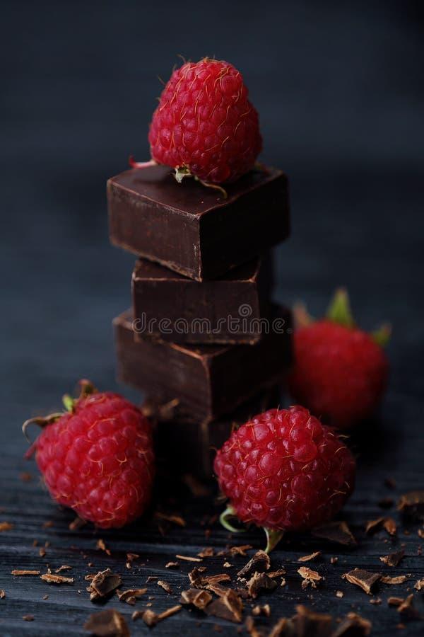 Läcker mörk choklad och mogna rosa hallon arkivfoton