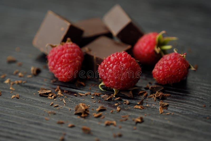 Läcker mörk choklad och mogna rosa hallon royaltyfria foton