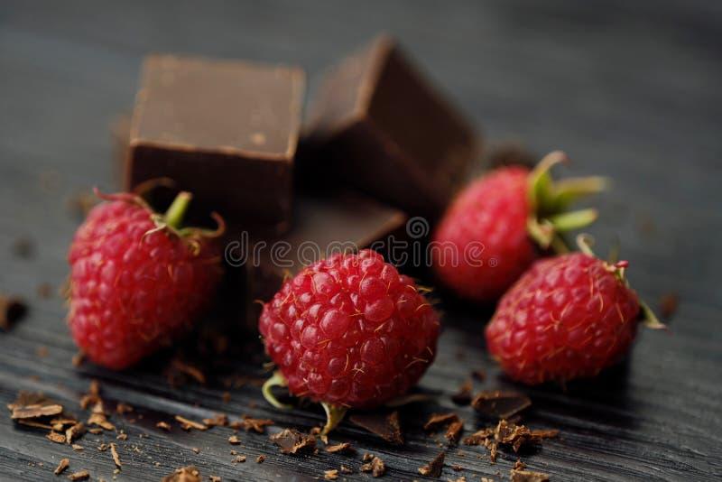 Läcker mörk choklad och mogna rosa hallon royaltyfri foto