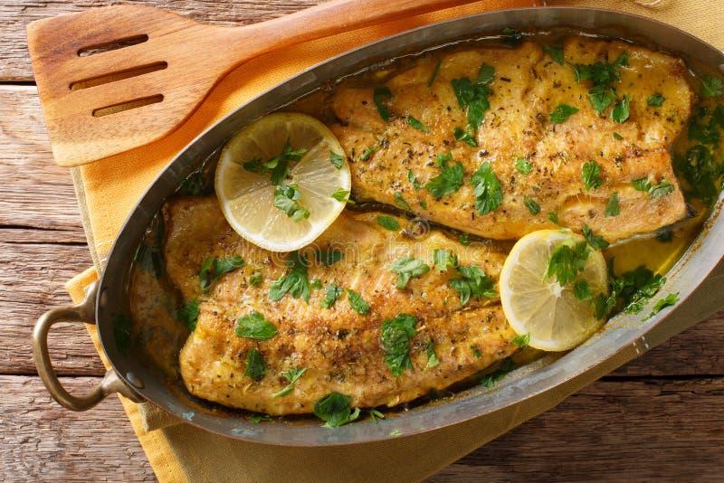 Läcker mat: forellfisk med sås för vitlökcitronsmör, parsl royaltyfria bilder