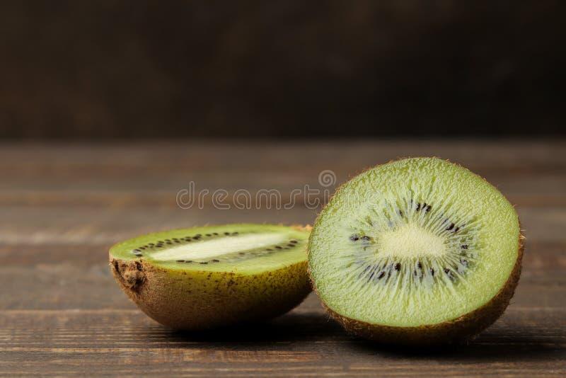 Läcker mogen kiwi och kiwi i ett snitt på en brun trätabell Närbild Utrymme för text royaltyfri fotografi