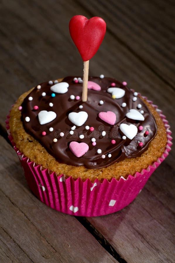 Läcker muffin med choklad- och sockerhjärtor royaltyfria bilder