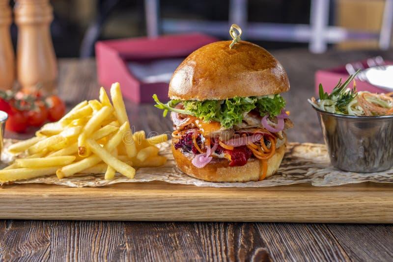 Läcker ny hamburgare med höna, sås och franska småfiskar på ett träbräde, lantlig stil, snabbmat royaltyfri fotografi