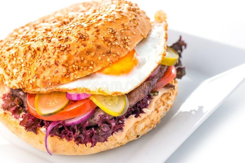 Läcker original- amerikansk hamburgare med det grillade nötkött, ägget och grönsaker på den vit plattan, mellanmålet eller lunch, arkivfoton