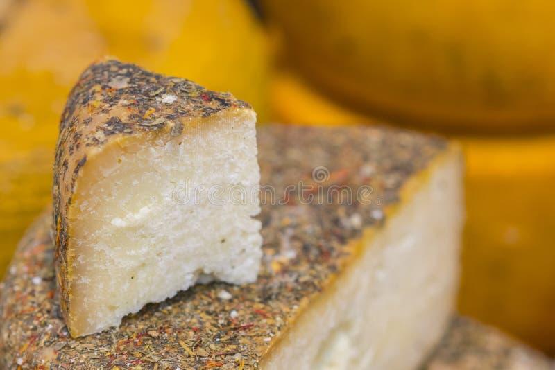 Läcker ost på kuggehylla i lager Isolerade objekt Hantverkost på lagrets räknare Stycken av ost med objekt som ska göras royaltyfri bild