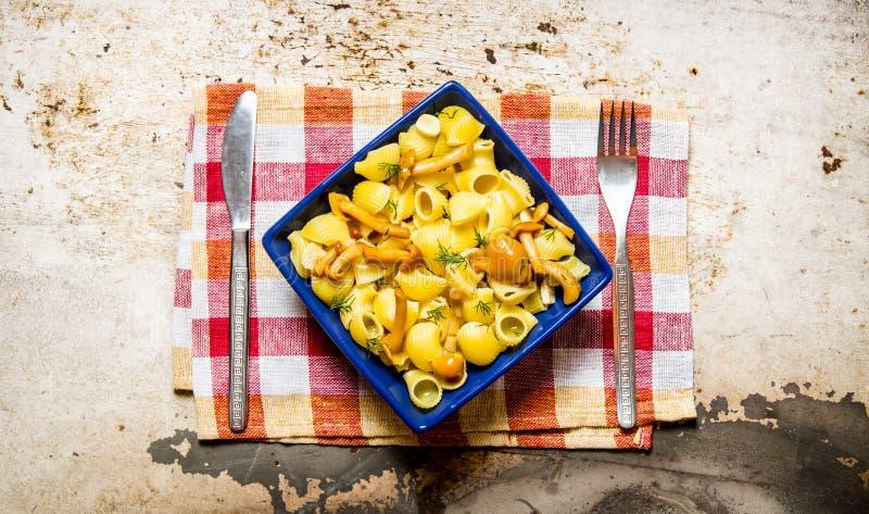 Läcker pasta med champinjoner på en platta på tyget arkivfoto