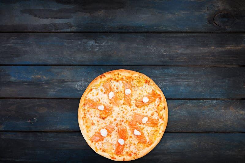 Läcker pizza med laxen och Philadelphia ost på en mörk träbakgrund Bottenriktning för bästa sikt royaltyfria bilder