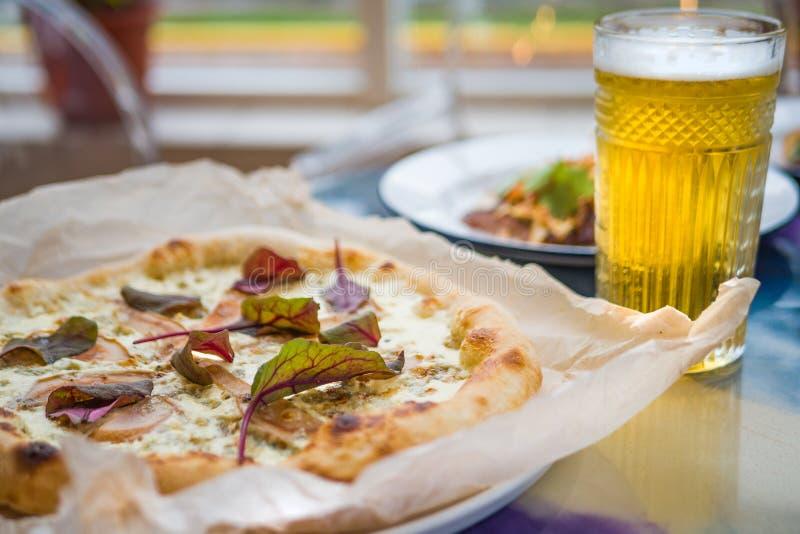 Läcker pizza med ost och päronet med sidor av gräsplan på tabellen arkivfoto