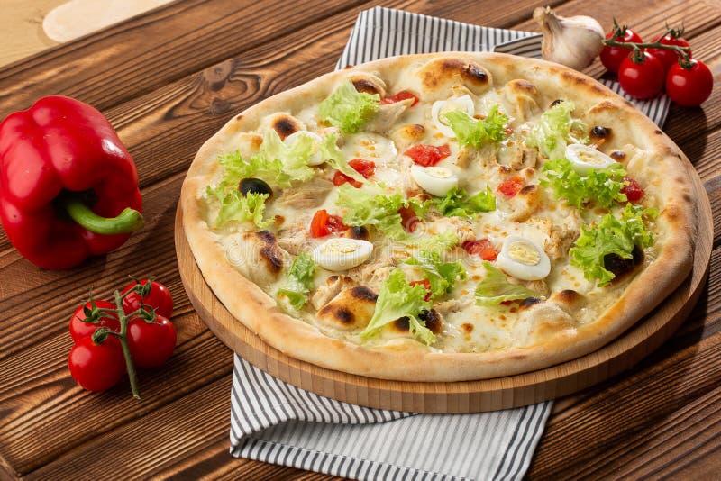 Läcker pizzaCaesar stil med vit sås, höna, parmesan, ägget, körsbärsröda tomater och ny grönsallat på träbakgrund arkivbild