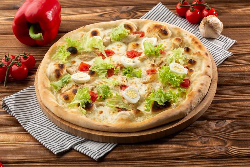 Läcker pizzaCaesar stil med vit sås, höna, parmesan, ägget, körsbärsröda tomater och ny grönsallat på träbakgrund royaltyfria foton