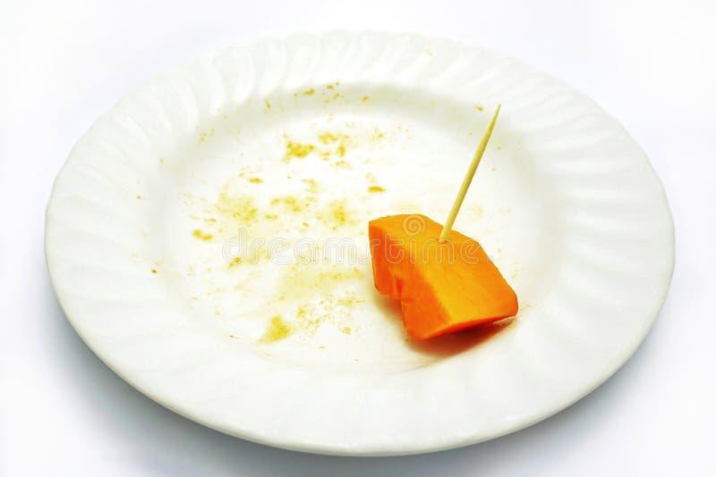 Läcker söt papaya, det sista stycket med den lilla pinnen som är klar att välja på en vit platta som isoleras på vit bakgrund royaltyfri fotografi