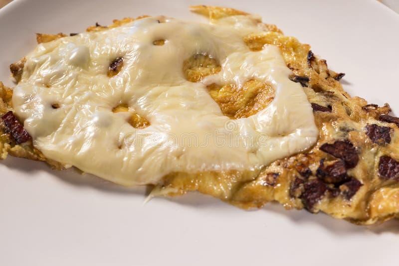 Läcker salamikorv och ostomelett på en platta arkivfoton