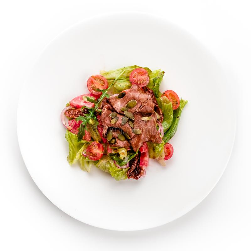 Läcker sallad för grönt kött med den grillad saftig biff, tomaten och gräsplansås i en vit platta som isoleras på vit arkivfoton