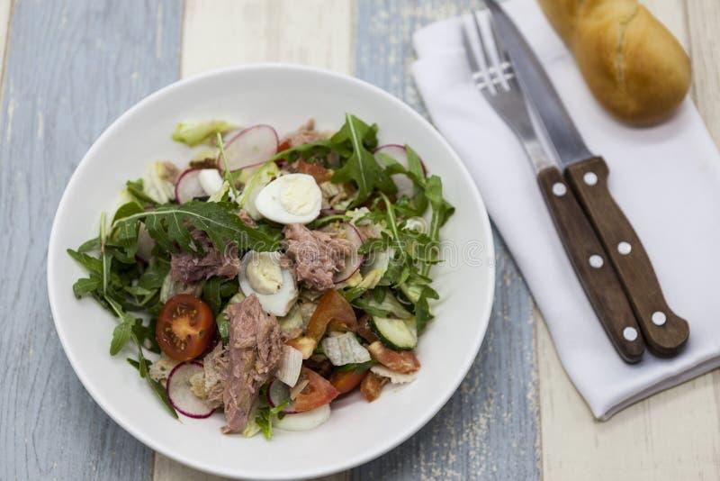 Läcker sallad för ny grönsak med tonfisk på den vita porslinplattan med gaffeln och kniven royaltyfria foton