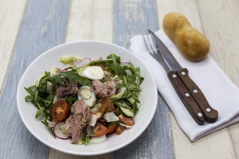 Läcker sallad för ny grönsak med tonfisk på den vita porslinplattan med gaffeln och kniven arkivbilder