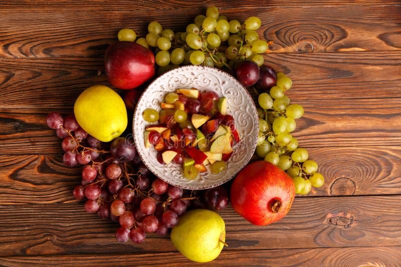 Läcker sallad i en platta av frukt på en trätabell royaltyfria bilder