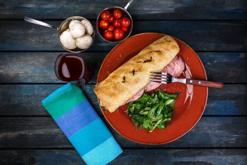 Läcker smörgås med skinkachampinjoner och grön sallad på en keramisk platta Kulör träbakgrund Top beskådar arkivfoto