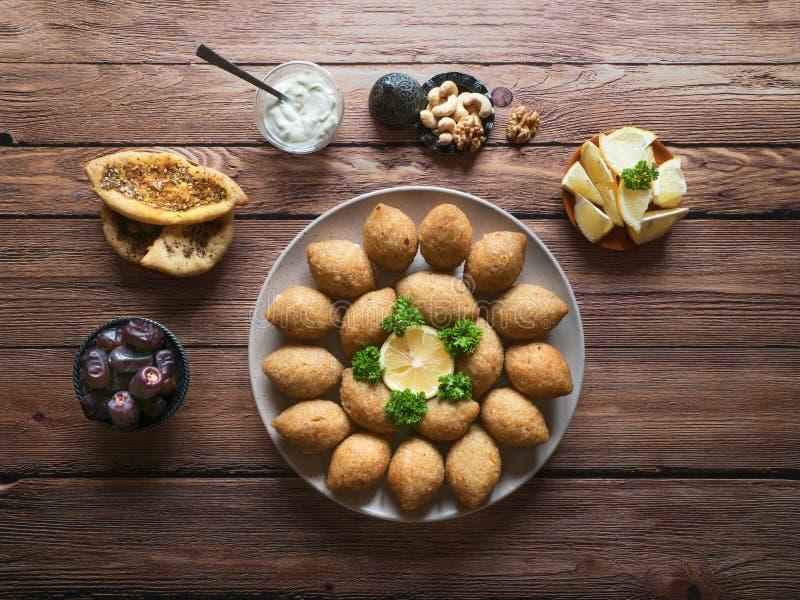 Läcker stekt kibbeh med yoghurtsås i en bunke som tjänas som på en platta på den gamla trätabellen Klassiskt libanesiskt recept arkivfoto