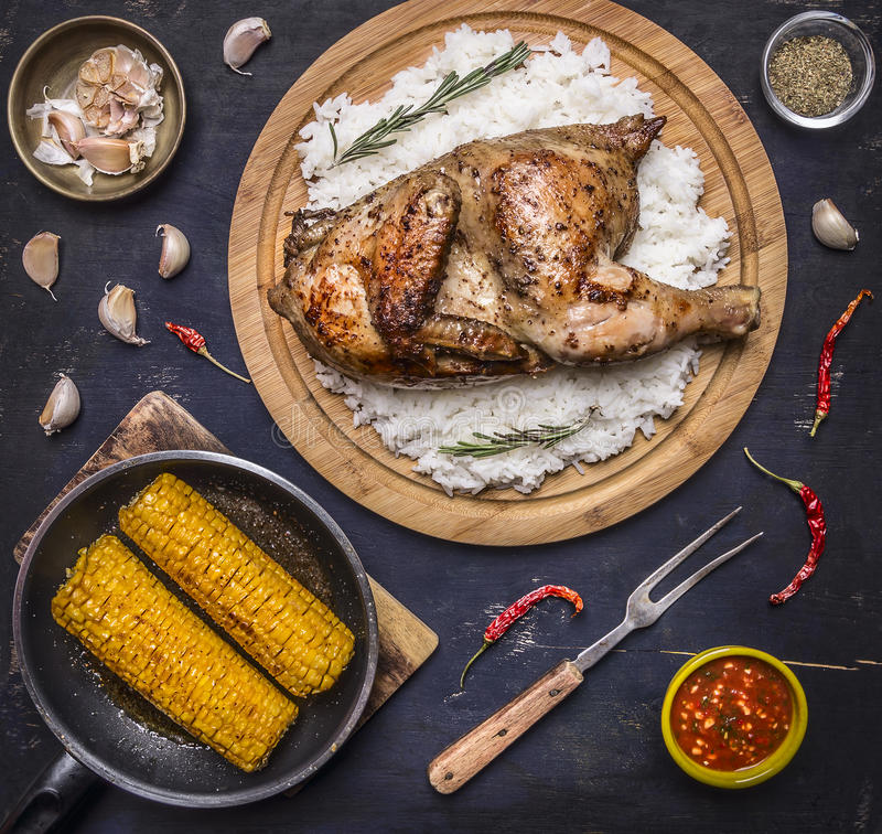 Läcker stekt kyckling med ris på en skärbräda, gaffel för kött, kryddig sås, kryddor, vitlök och havre i pannan på mörker - blått royaltyfri foto