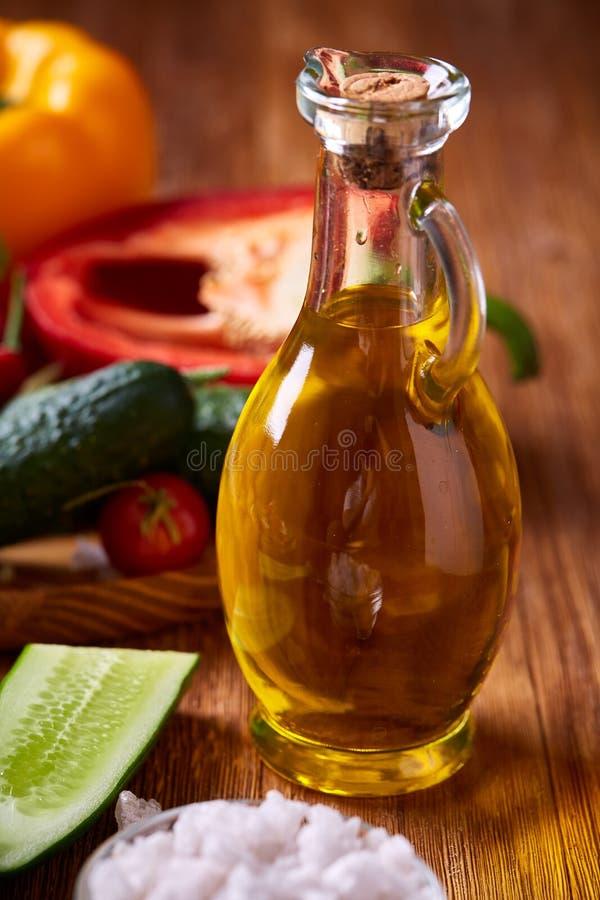 Läcker stilleben med guld- olivolja i den glass kruset bland nya grönsaker, närbild, selektiv fokus royaltyfria foton