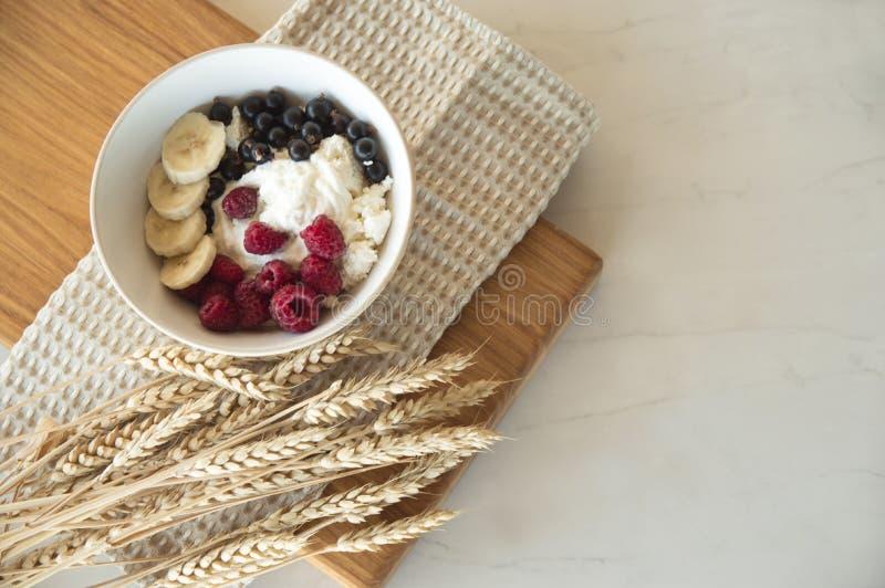 Läcker sund frukost av keso med bär En vit platta med keso- och bärställningar på ett träbräde arkivfoto