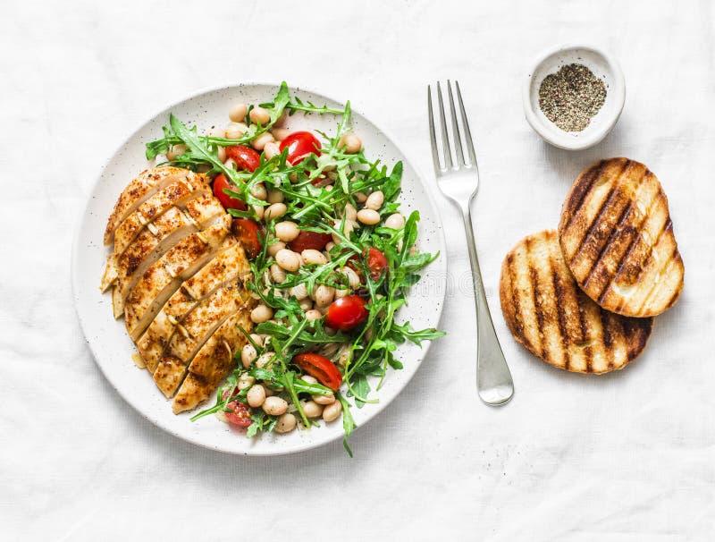 Läcker sund lunch - bakade fegt bröst och vita bönor, arugula, sallad för körsbärsröda tomater på en ljus bakgrund fotografering för bildbyråer