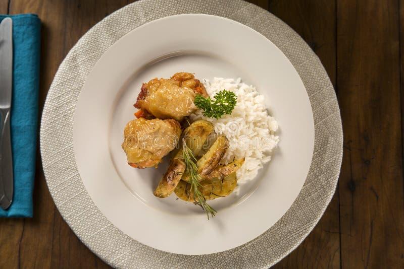 Läcker sund mat med grillad höna, lantliga potatisar och ris på plattan övre sikt royaltyfri fotografi