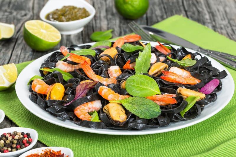 Läcker svart nudelsallad med räkor, musslor, ny gräsplan royaltyfri bild