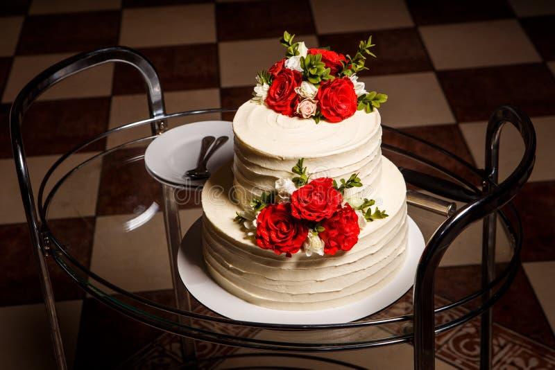 Läcker två-tiered bröllopstårta på exponeringsglasmagasinet med plattor och skedar arkivbilder
