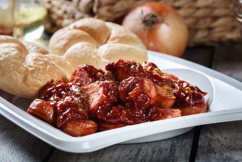 Läcker tysk currywurst - stycken av korven med currysås royaltyfri foto