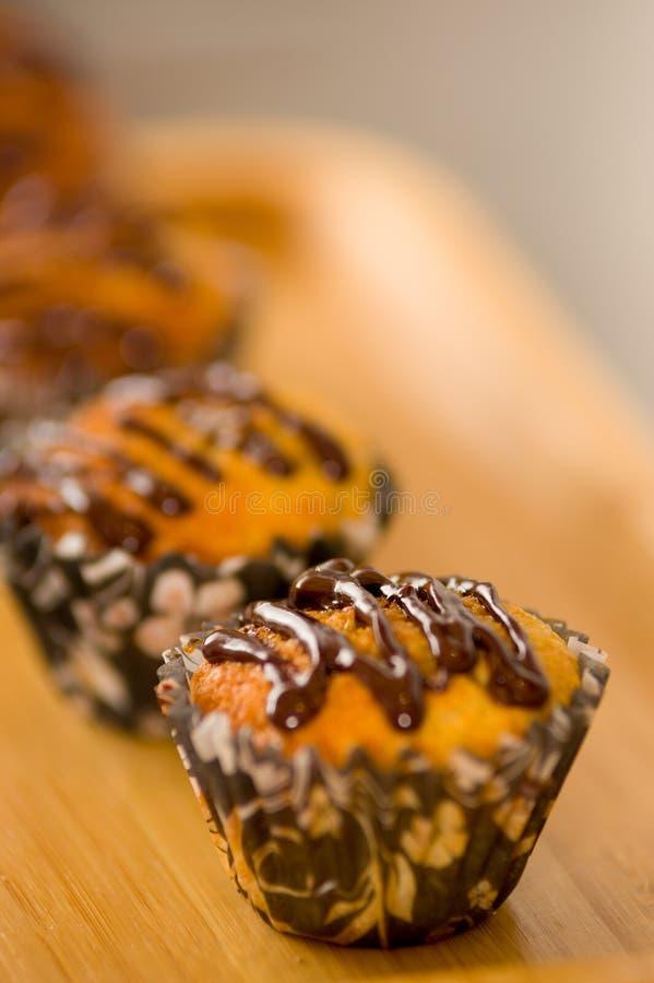 Läcker vaniljmuffin med chokladpralinsirap i en träbakgrund royaltyfria foton
