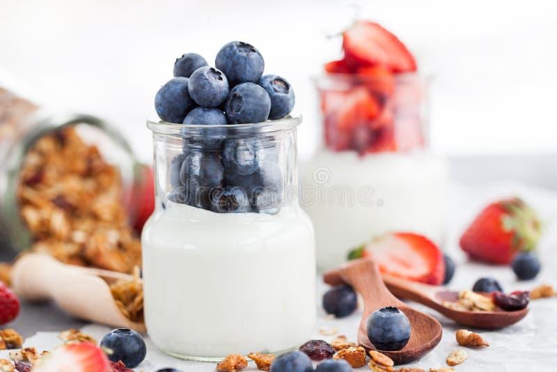 Läcker vanlig yoghurt med det nya blåbäret och jordgubben i a arkivfoton
