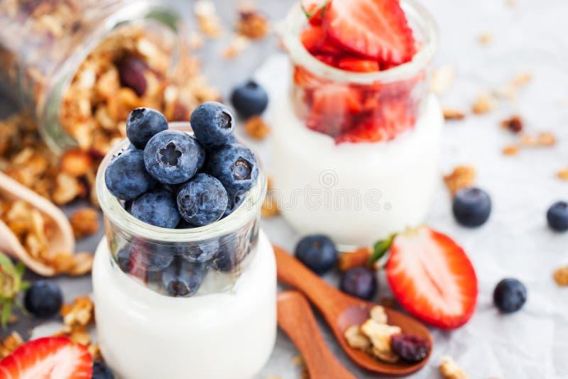 Läcker vanlig yoghurt med det nya blåbäret och jordgubben i a arkivbild