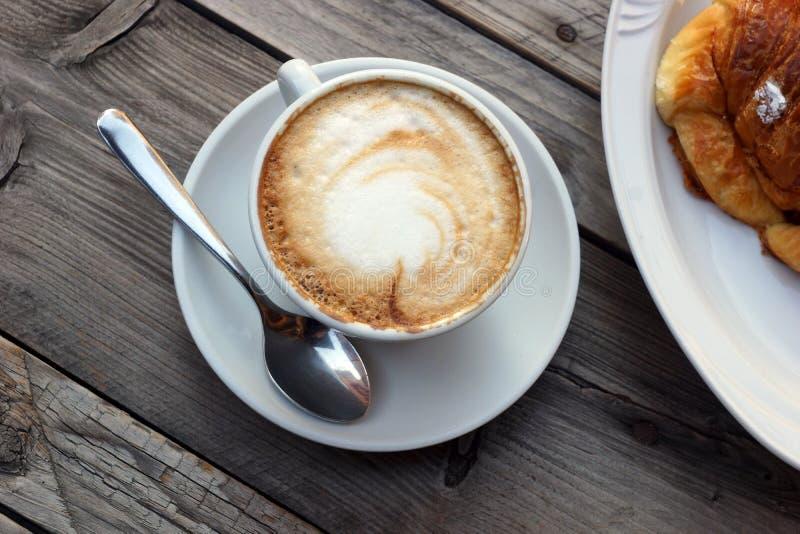 Läcker varm italiensk cappuccino står i en kopp med ett tefat på en trätabell I bakgrunden en ny giffel på en platta arkivbilder