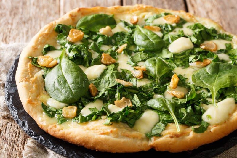 Läcker varm pizza med ny spenat-, vitlök- och ostnärbild på ett bräde horisontal fotografering för bildbyråer