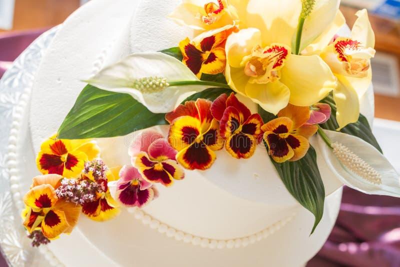 Läcker vit tiered bröllopstårta med blommor royaltyfri foto