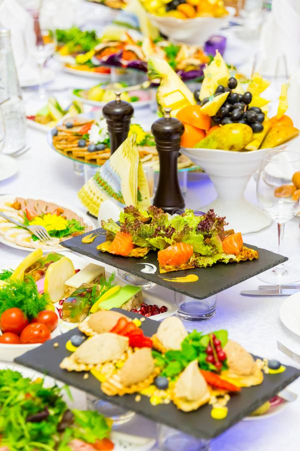 Läckerheter, mellanmål och frukt på den festliga tabellen i restaurangen Beröm catering sallader för fruktsaft för druvor för fru arkivfoton