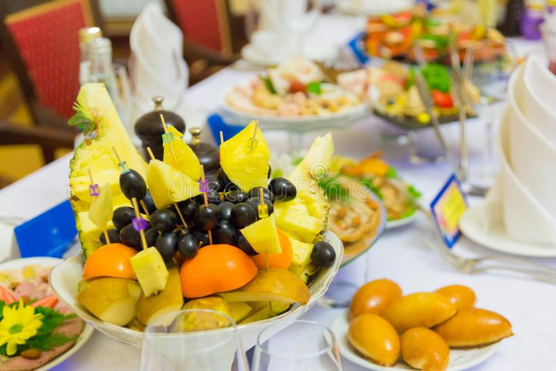 Läckerheter, mellanmål och frukt på den festliga tabellen i restaurangen Beröm catering sallader för fruktsaft för druvor för fru royaltyfri foto
