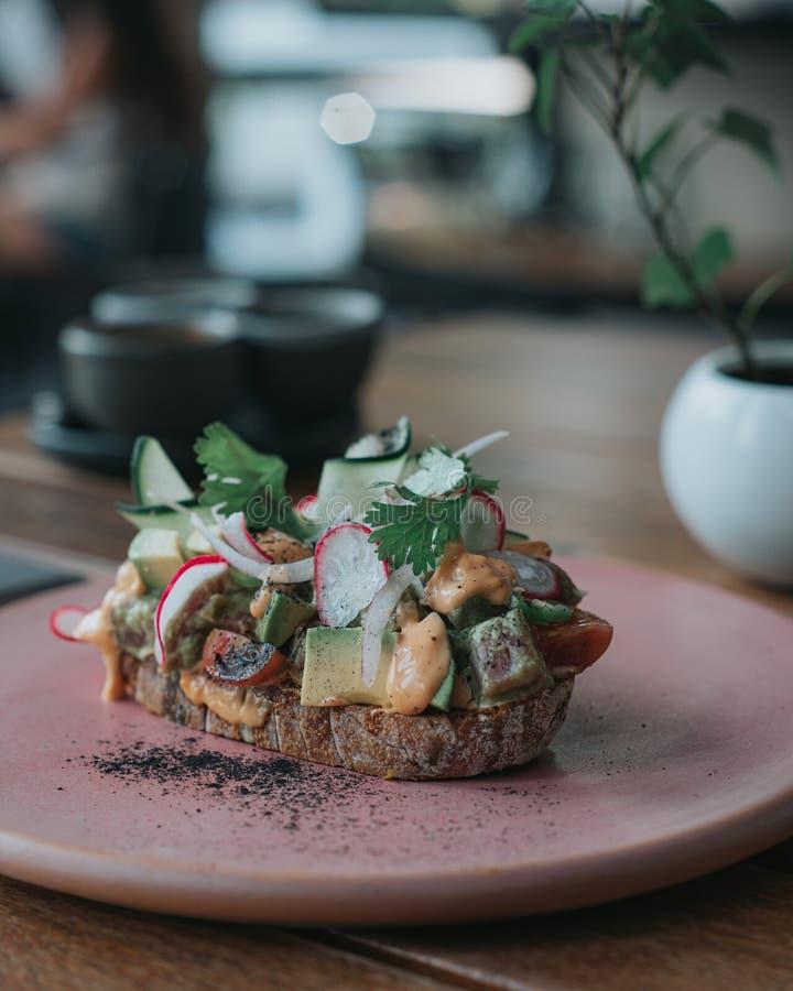 Läckert avokadorostat bröd med artisanal bröd på en rosa platta royaltyfri fotografi