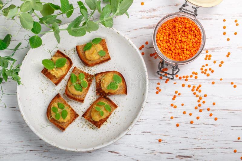Läckert brödrostat bröd med det hummuspate, pasta, doppet av linser och morötter med ärtagroddar på en vit platta royaltyfria bilder
