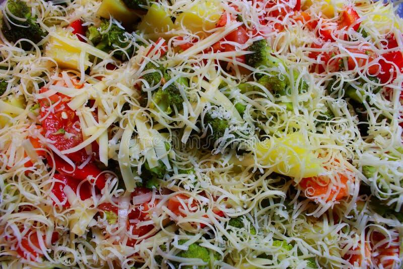 Läckert grönsakmål med röd peppar för broccolitomatlök under grated ost som sund ny vegeterian matbakgrund royaltyfria foton