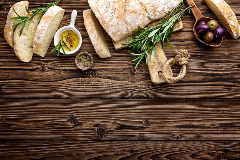 Läckert hemlagat italienskt ciabattabröd med olivolja och oliv på trälantlig bakgrund, ovanför sikt, utrymme för text royaltyfri bild